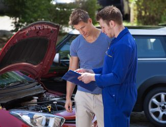 Mechanic Showing Clipboard To Customer By Breakdown Car