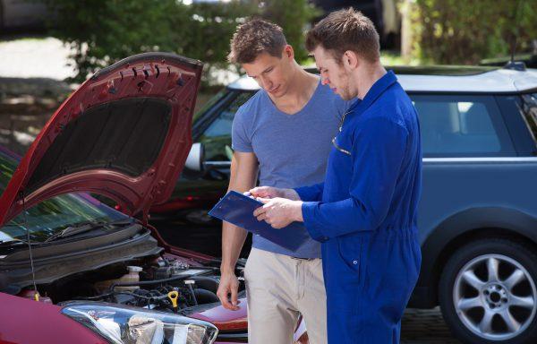 Mechanic Showing Clipboard To Customer By Breakdown Car